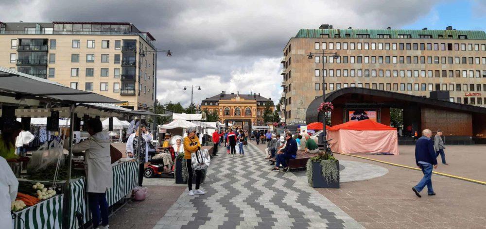 Torikojuja, ihmisiä ostoksilla ja taustalla siintää Joensuun taidemuseo Onni